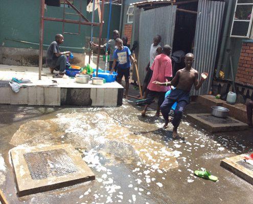 Children cleaning their compound