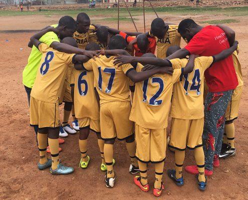 Street children pray before they play foot balls