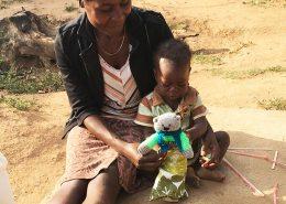 Young girl receiving a teddy bear