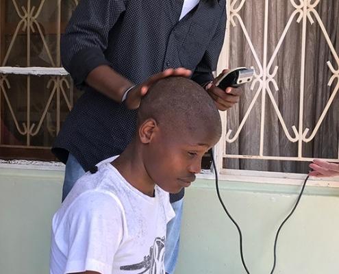 A street boy getting a haircut