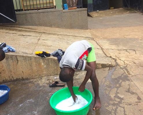 Ugandan street boy washing clothes