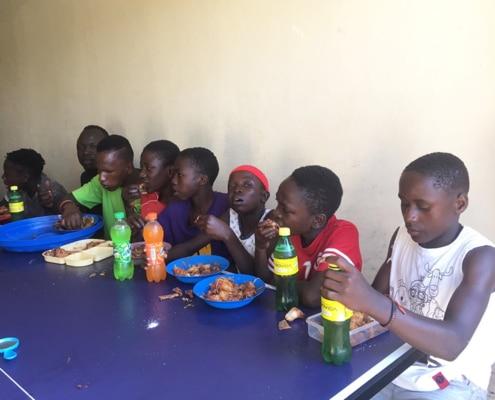 Ugandan children eating chicken