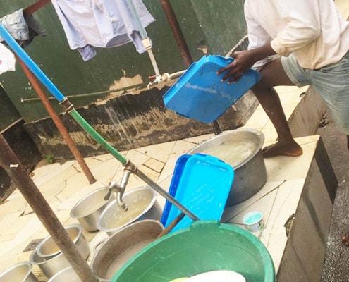 A former street boy washing dishes