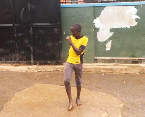 Street boy in Uganda playing football