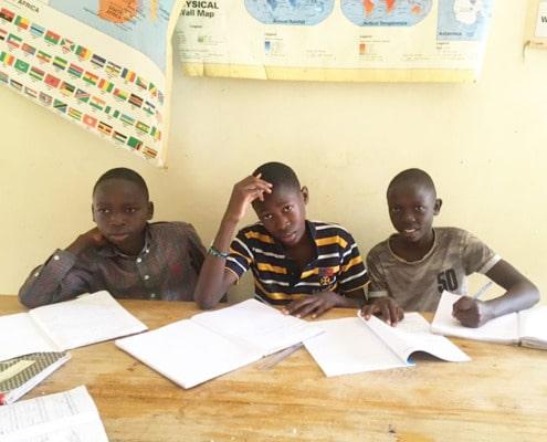 Three former street children at school