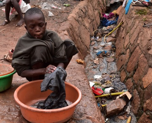 Street boy washing his clothes next to open sewer