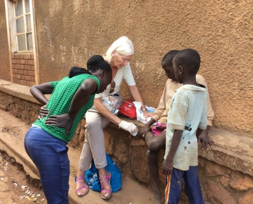 Jane doing first aid for a street child