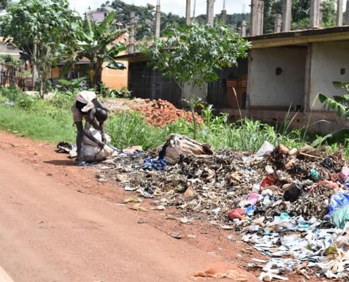 Man picking through rubbish in Kampala