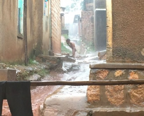 A child showering in the rain in Kampala