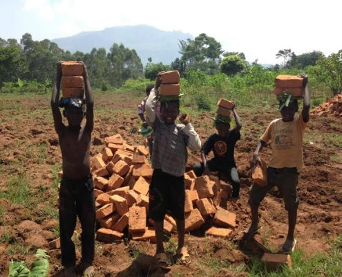 Children helping build house by carrying bricks