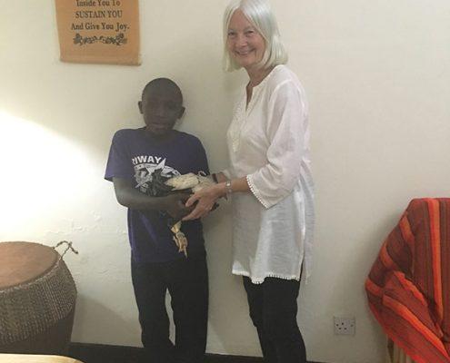 Street boy giving Jane a hen