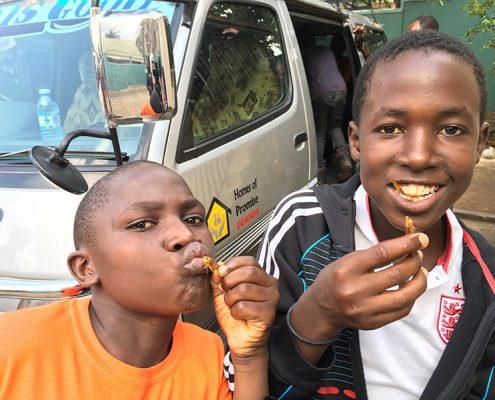 Two of the street children enjoying fried grasshoppers