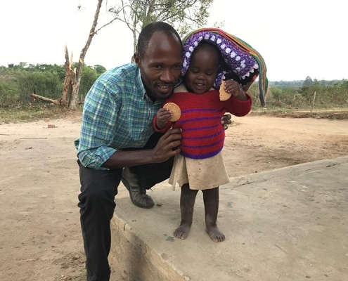 Ugandan girl with a donated jumper and blanket