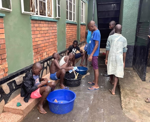 Street boys cleaning their shoes