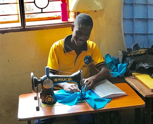 One of our boys making clothes