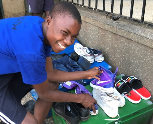 A street boy with donated shoes