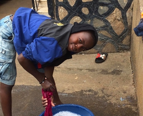Street boy washing his clothes