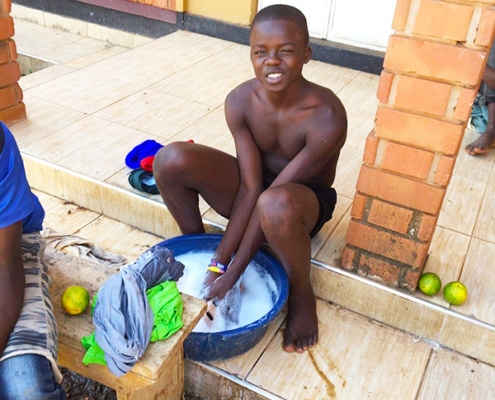 Former street child washing his clothes